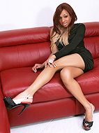 Alluring transsexual Bella posing on the sofa