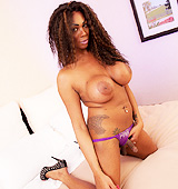 Busty chocolate tgirl Paris strips on the bed